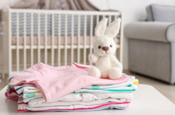 На заднем плане детская кроватка. На переднем - стопка одежды и мягкий заяц