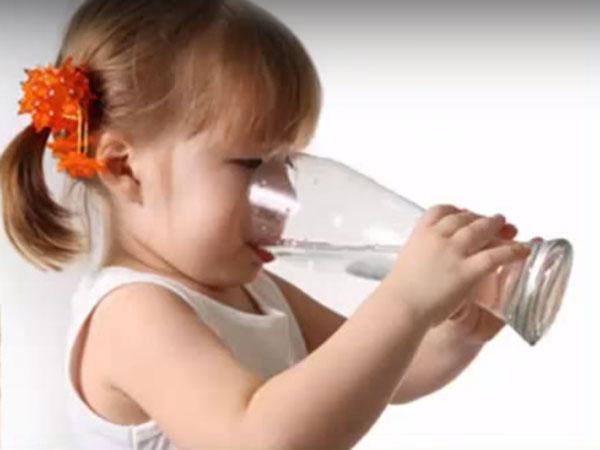 Девочка пьет воду из большого бокала
