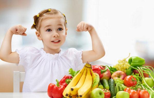Девочка показывает, какая она сильная. На столе лежат фрукты и овощи