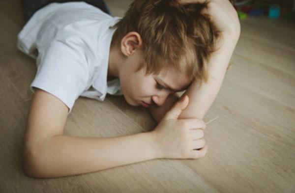Расстроенный мальчик лежит на полу
