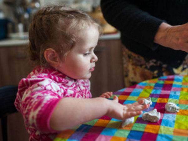 Девочка играет с кусочками теста