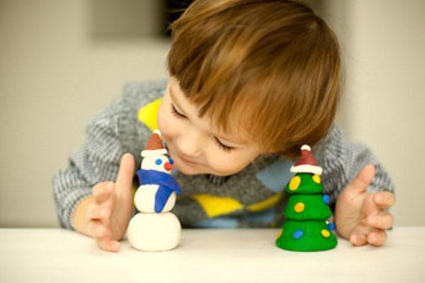 Ребенок рассматривает слепленного снеговика и елку