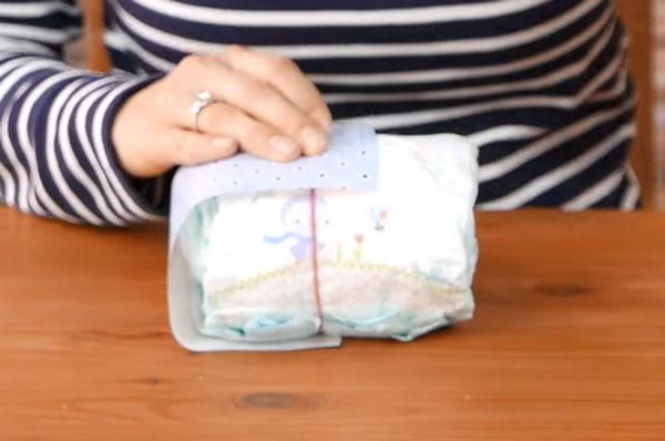 Скрученные подгузники оборачивают бумагой