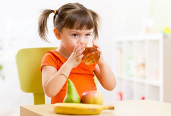 Девочка пьет яблочный сок. На столе лежит банан, груша и яблоко