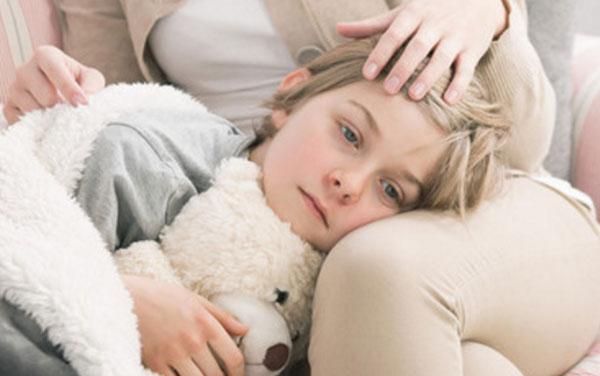 Девочка с красными щеками лежит на коленях матери