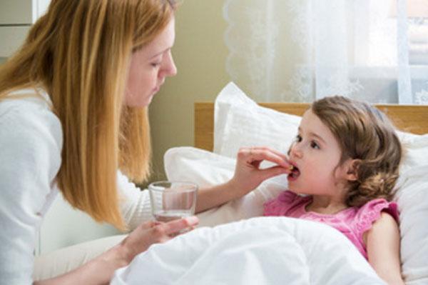 Мама дает дочери таблетку. Девочка лежит в кровати