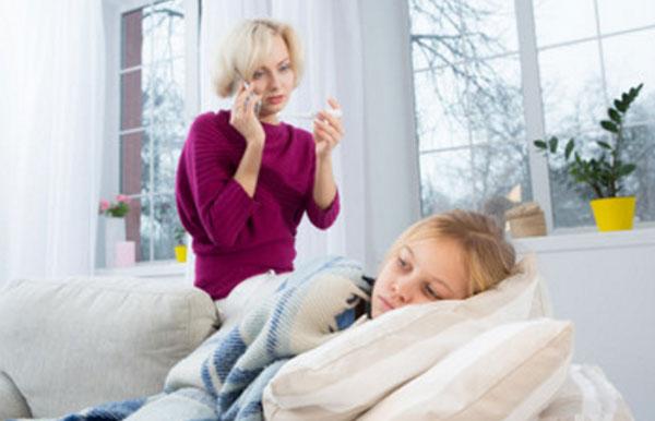 Девочка лежит в постели. Мама стоит сзади дивана и смотрит на градусник