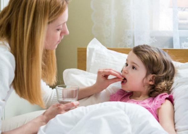 Девочка лежит в кровати. Мама ей дает таблетку