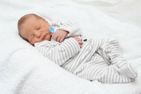 Новорожденный ребенок сладко спит, сжимая в своей ручке чайную ложечку