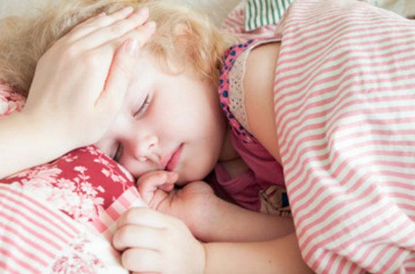 Девочка спит. Мама трогает ее лобик