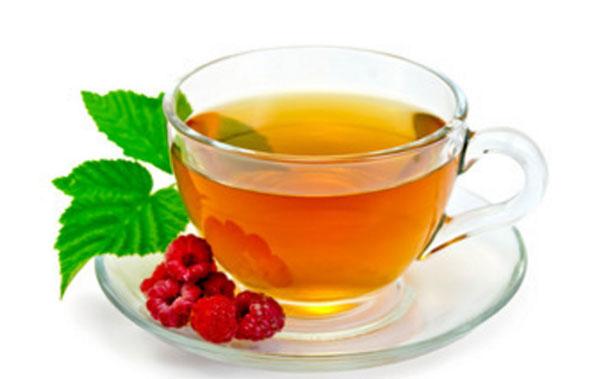 Малиновый ай в чашке. На блюдечке лежат ягоды и листья малины