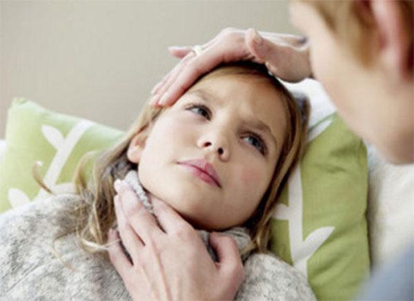 Больная девочка лежит в постели. Мама трогает ее голову