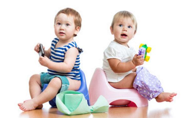 Два ребенка сидят на горшках. Рядом лежит рулон туалетной бумаги