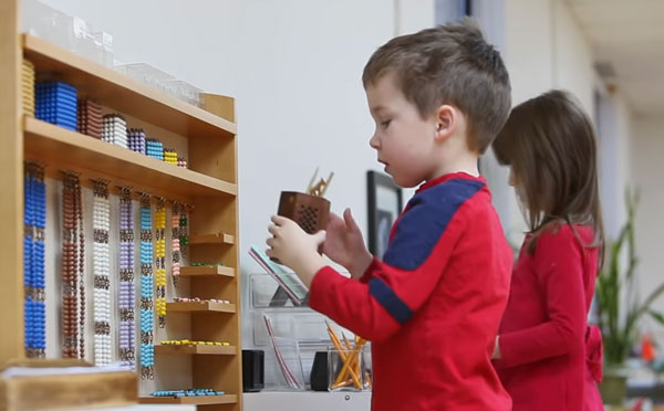 Мальчик и девочка стоят возле стенда с материалами