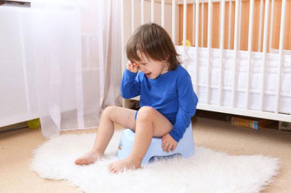 Мальчик сидит на горшке и плачет