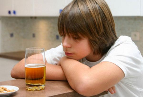 Мальчик сидит за столом. Перед ним стоит бокал пива, он на него томно смотрит