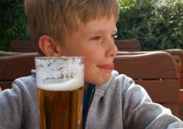 Мальчик сидит возле бокала безалкогольного пива и облизывается