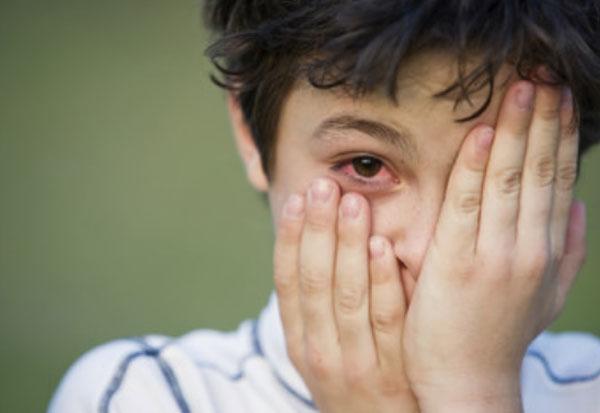 Мальчик одной рукой прикрывает свой глаз. Другая приопущена и видно, что один глаз красный