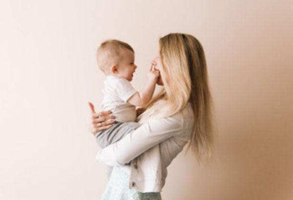 Ребенок у мамы на руках, трогает ее лицо