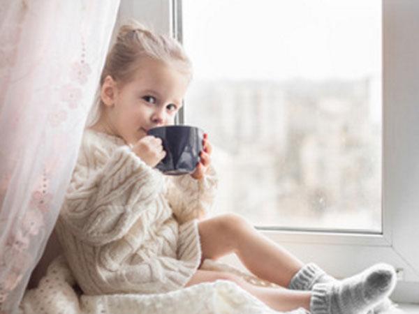 Девочка сидит на окне с чашкой в руках. Она что-то пьет