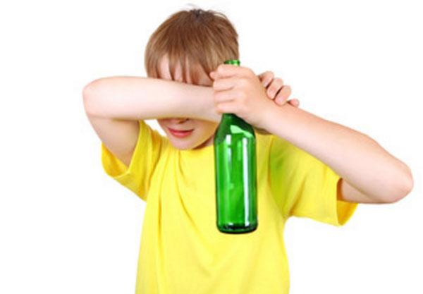Мальчик с пустой бутылкой от пива в руках прячет свои глаза