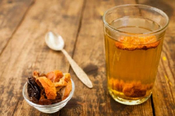 На столе стоит стакан с компотом из сухофруктов. Рядом лежит ложечка и маленькая креманка с сухофруктами
