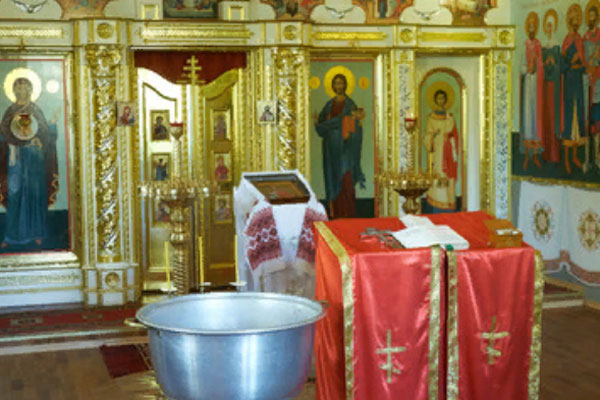 Библия, православный крест и чаша, приготовленные для церемонии крещения