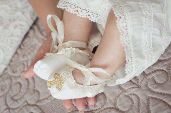 Ножки грудного ребенка. На них тканевые туфельки белого цвета с изображением золотого креста