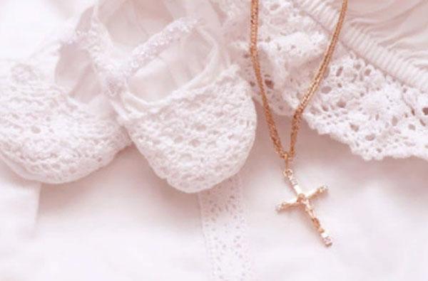 Белое детское одеяние и золотой крестик на цепочке