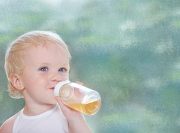 Маленький ребенок пьет яблочный сок с бутылочки