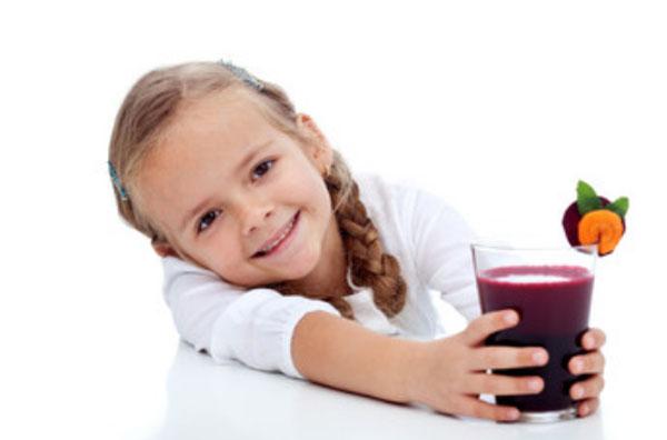 Девочка держит стакан со свекольным соком и улыбается