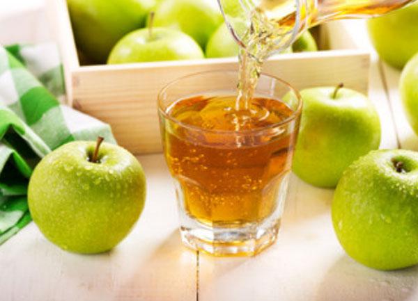 Стакан яблочного сока. Рядом зеленые яблоки