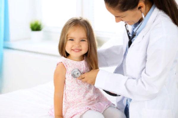 Доктор слушает грудную клетку девочки