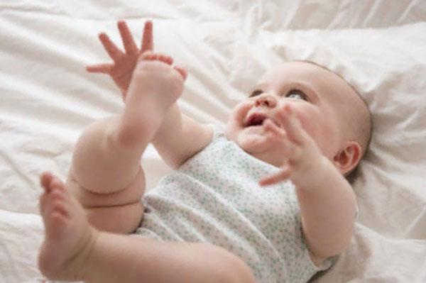 Радостный грудной ребенок лежит на спинке