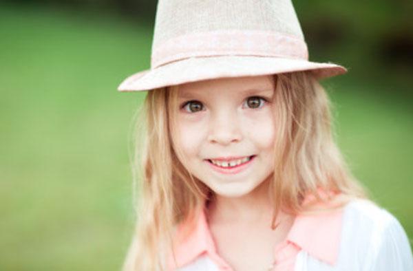 Пятилетняя девочка в шляпке. Она улыбается