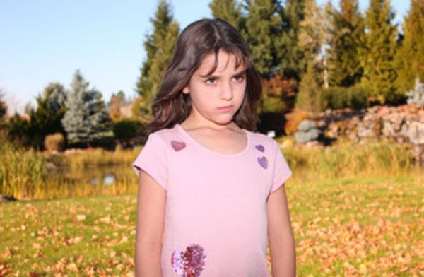 Сердитая девочка стоит на поляне