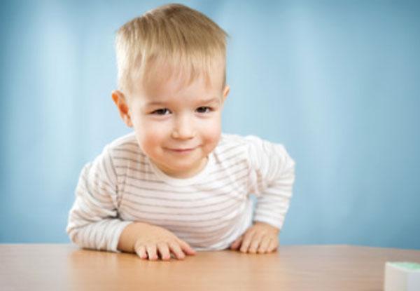 Двухлетний малыш облокачивается на стол