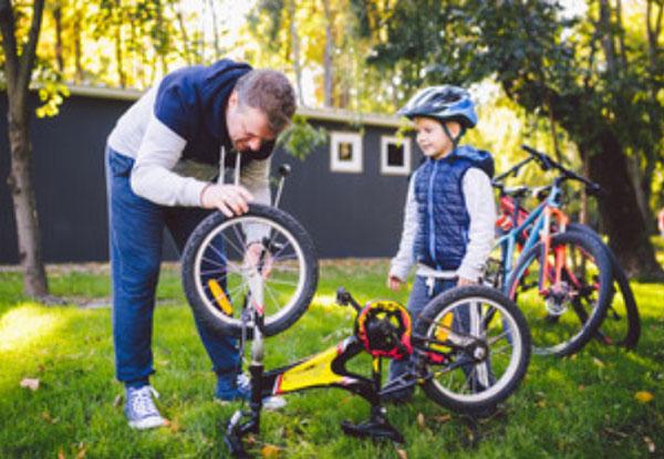 Папа чинит велосипед. Мальчик следит за его работой
