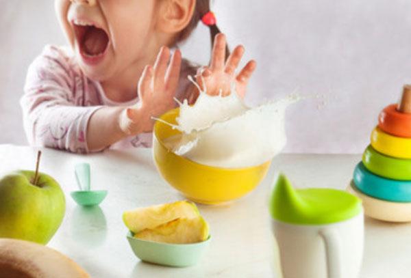 Девочка отталкивает тарелку. Сейчас разольется молоко