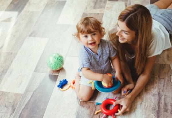 Мама с ребенком сидят на полу и играют игрушками