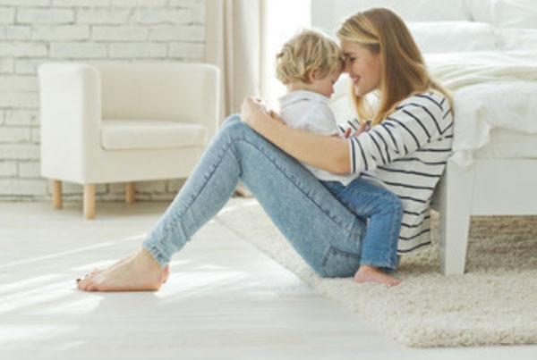 Ребенок сидит на маме. Она смотрит ему в глаза