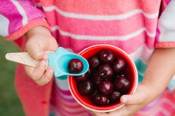 Ребенок держит мисочку с неочищенными черешнями и ложечку, в которой уже лежит одна ягода
