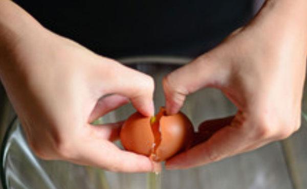 Над миской разбивают яйцо