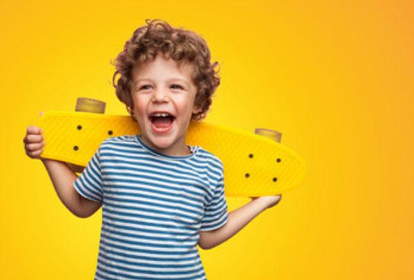 Счастливый мальчик держит скейт за спиной
