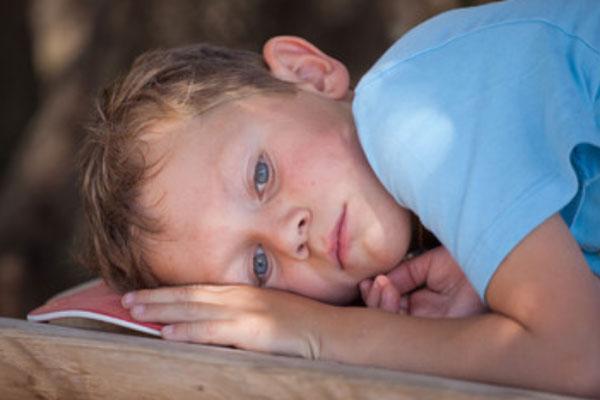 Изнеможденный мальчик лежит
