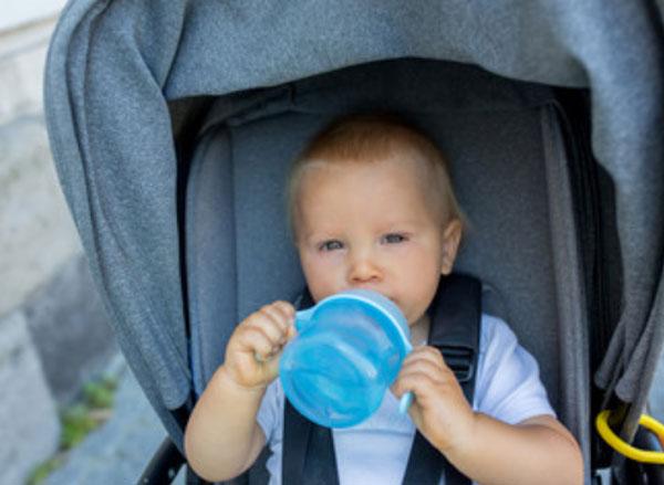 Маленький ребенок сидит в коляске и пьет из чашки -непроливайки
