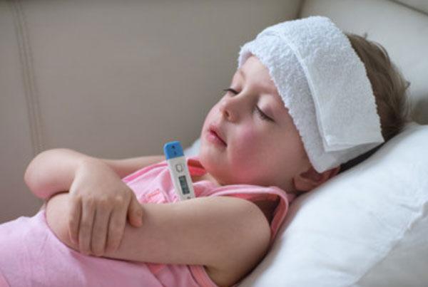 Ребенок лежит в постели. На голове смоченное полотенце. Под мышкой - градусник