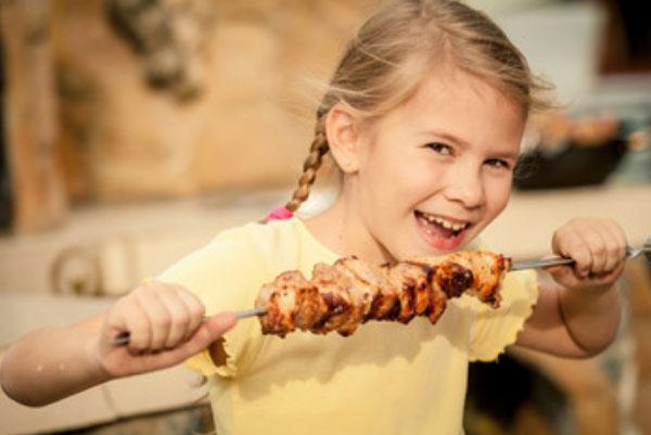 Девочка держит в руке шампур с нанизанным мясом