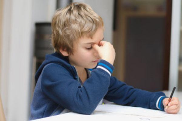 Ослабленный ребенок сидит за столом