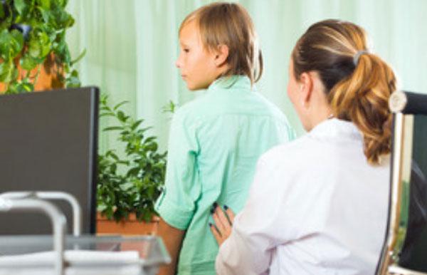 Доктор пальпирует поясничную область ребенка